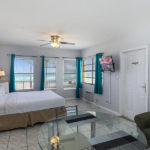 guest room with one bed, living area, and beach view at Hollywood Beach Hotels